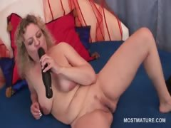 Slutty mature babe sucking dildo and rubbing pussy in bed