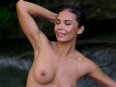 Nude MILF doing yoga next to a waterfall